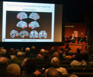 Dr. Dave Wolk is gestures a screen with brain imaging on it as he presents in front of a large audience.