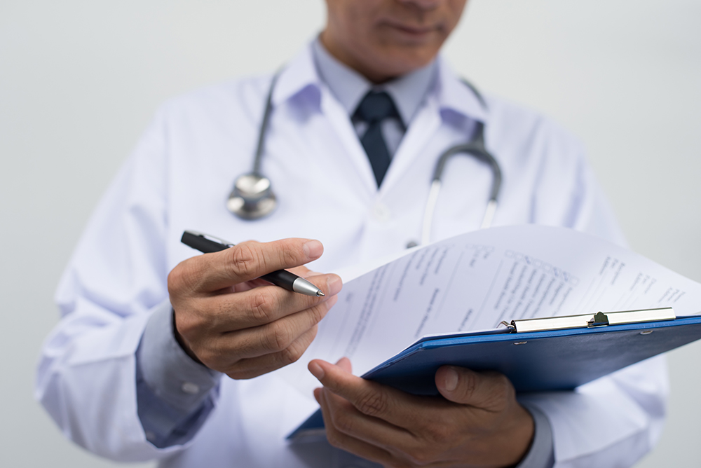 Male doctor writing perscription