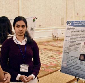 Lasya Sreepada standing in front of her research poster.