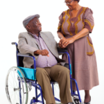 An older man in a wheelchair looks lovingly at an older woman who is holding his hand.