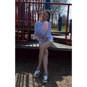 Xueying Lyu sitting on a playground with her legs crossed. She is holding a cotton candy.