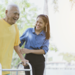 Younger woman helps older man walk with walker.
