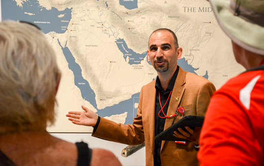 Yaroub Al-Obaidi speaking to people in front of a map of the Middle East.